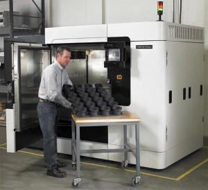 Ingeniero mostrando bandeja de piezas impresas en 3D con  Fortus 900mc